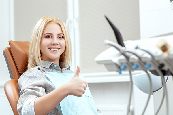 Routine checkup done. Beautiful cheerful young woman showing thumbs up and smiling sitting at the dental chair at the dentist office